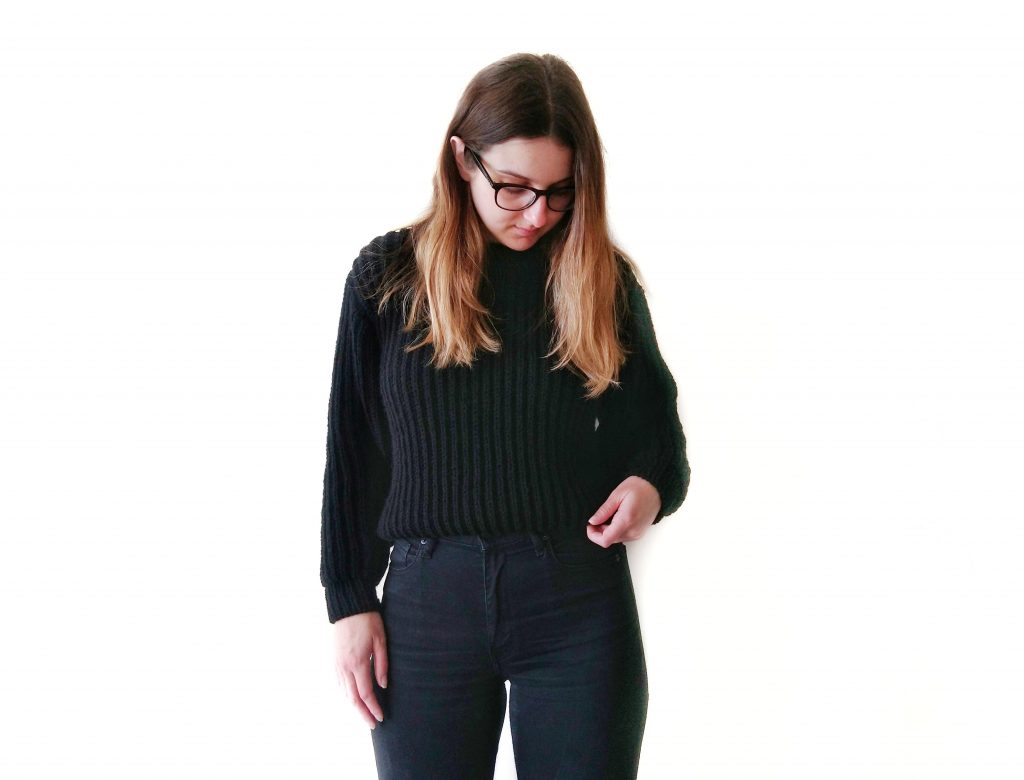 Jess, Founder of Knits Please is wearing the black September Sweater she knit from Petite Knit's knitting pattern, with black jeans. She is standing in front of a white background.
