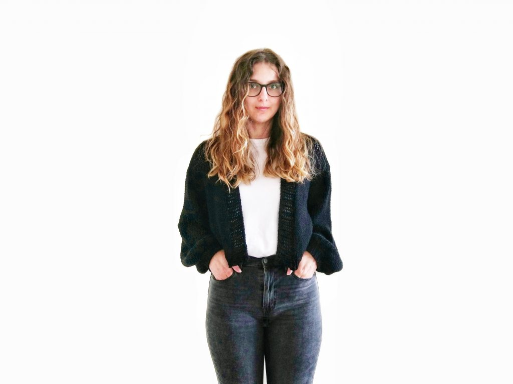 A photo of Jess against a white background wearing jeans, a white t-shirt and a black, cropped knit cardigan with loose sleeves, hand knit from Knitatude's Top Gun Bomber pattern